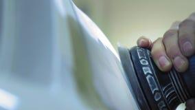 Linterna que pule, proceso de las luces del coche Un trabajador del servicio del coche pule la linterna de un vehículo de pasajer almacen de metraje de vídeo