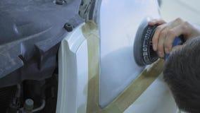 Linterna que pule, proceso de las luces del coche Un trabajador del servicio del coche pule la linterna de un vehículo de pasajer metrajes
