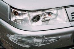 Linterna quebrada de la lámpara y coche de parachoques rasguñados con daño profundo Imagenes de archivo