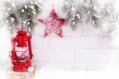 Linterna roja decorativa, frontera del árbol de la piel de las ramas con la estrella roja en el fondo blanco del ladrillo La Navi imagen de archivo