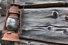 Linterna vieja oxidada en la pared de madera Imagen de archivo