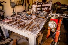 Linterna y manillar de viejo Rusty Motorcycle en la vertiente con viejo Rusty Tools imagen de archivo libre de regalías