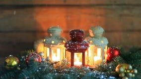 Linternas ardiendo con la decoración y caer de la Navidad abajo copos de nieve reales metrajes