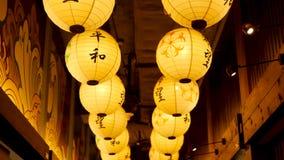 Linternas de papel que brillan en la calle Linternas de papel hermosas que brillan mientras que cuelga en paso estrecho en la cal metrajes