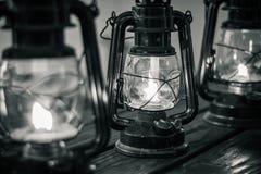 Linternas del aceite en la tabla de madera en blanco y negro imagen de archivo