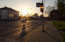 Linternas del borde de la carretera y grúas del puerto contra el contexto de una puesta del sol en Klaipeda, Lituania foto de archivo