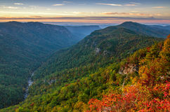 Linville Gorge, Sunrise, North Carolina. The warm light from the rising sun just begins to bathe the early autumn foliage. This image was taken from Wiseman view Royalty Free Stock Photography