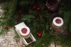 Linzer-Plätzchen in einer Weihnachtsdekoration auf einer Holzoberfläche lizenzfreies stockfoto