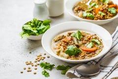 Linzesoep met groenten in een witte plaat, witte verticale achtergrond, Installatie gebaseerd voedsel, het schone eten stock afbeeldingen