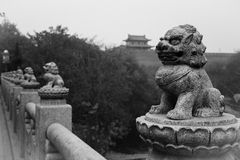 The Lion and the ancient stone. Carved stone lions on the bridge and distant ancient royalty free stock image
