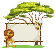 A lion and a bee near a big tree Stock Photos