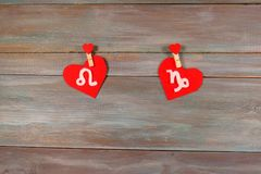 Lion and Capricorn. signs of the zodiac and heart. wooden backgr. Ound. card. unusual handwork stock photo