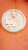 Lion in circular shape bas relief art on orangel wall Royalty Free Stock Photo