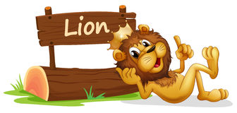 A lion with a crown relaxing beside a signboard Royalty Free Stock Photo