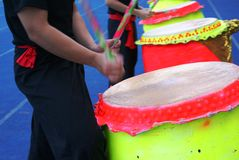 Lion dance drummers. Two lion dance troupe members wearing black uniform beating on their drums. Drums are coloured bright yellow and red stock photo