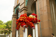 Lion dance. Ho Chi Minh,Vietnam. Before starting new business ritual called `Lion dance` against evil spirits is performed. It is custom that has origin in China Stock Photos