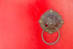 Lion Door Knocker. A lion head door knocker made from brass stands guard on this bright red door Stock Image
