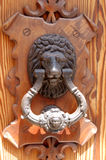 Lion door knocker. Lion head door knocker on an ornate wooden door Royalty Free Stock Image