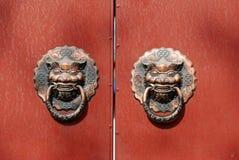Lion door knocker on red door stock photo