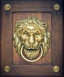 Lion door knocker. On wooden door royalty free stock photo