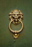 Lion Doorknocker on a Green Door. A gold doorknocker in the shape of a ferocious lion is mounted on a green door Stock Photos