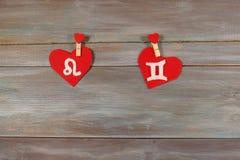Lion et jumeaux signes du zodiaque et de coeur Backgroun en bois Photographie stock libre de droits