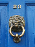 Lion face door knocker. A brass door knocker sculptured in the face of a lion Stock Image