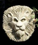 Lion face garden sculpture plaque. Decorative stonework plaque of lions head Stock Photos