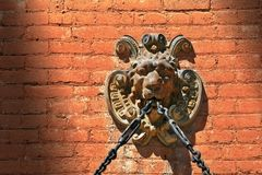 Lion Face Gargoyle with Chain on Brick Wall Stock Image