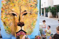 Lion face maked by two painted girls - participants of Rehovot International Live Statues Festival. REHOVOT, ISRAEL - JULY 4, 2018: Lion face maked by two royalty free stock image
