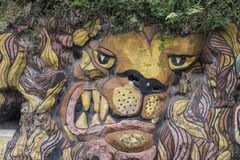 Lion graffiti on natural overgrown rock face, Barbedos. Very angry looking lion - three-dimensional - painted on escarpment - Barbados Stock Image