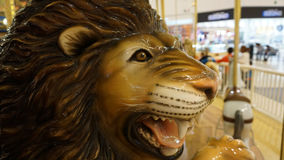 Lion head. A big fiber glass lion in a carousel, close up pf a lion head in a kids playground whit an out of focus background Stock Photo