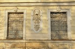 Lion head building exterior wall sculptural decoration. Vertical design of a lion grasping a ring in the jaws between the windows with old rusty grills bearing stock image