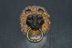 Lion head door knocker. On  wooden background Royalty Free Stock Image