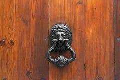 Lion Head Door Knocker. On wooden background stock photos
