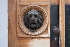 Lion head door knocker on wooden door. Antique lion head door knocker inset on aged wooden door with details stock image