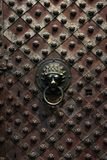Lion head doorknob on an old copper-riveted rusty patterned door at St. Vitus Cathedral in Prague. Czech Republic royalty free stock image