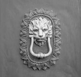 Lion head knocker on an old wooden door in Tuscany. Lion head knocker on an old wooden door in Tuscany – Italy, black and white royalty free stock image