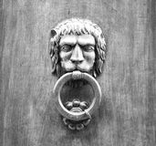 Lion head knocker on an old wooden door in Tuscany. Lion head knocker on an old wooden door in Tuscany – Italy, black and white royalty free stock photography