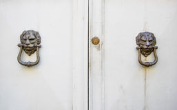 Lion head knockers on an old white wooden door Stock Photos