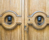 Lion head knockers on an old wooden door. royalty free stock photo