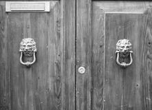 Lion head knockers on an old wooden door in Tuscany. – Italy, black and white royalty free stock image