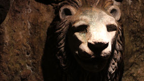 Lion head made of stone in a cave Stock Photography