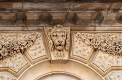 Lion head relief on the facade of building. London, UK. Lion head sculptures on wall old building decorations architecture in London, United Kingdom Royalty Free Stock Image
