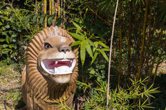 Lion head sculpture made of wood. In the park Stock Image