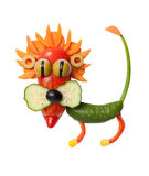 Lion made of cucumber, pepper and corn. Lion made of cucumber, pepper, carrot, corn and olive. Easy and fun way to make vegetable animal. Isolated background royalty free stock image