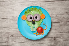 Lion made of vegetables on plate and wood Royalty Free Stock Images