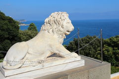 Lion marble sculpture. Park and the mountains near the Vorontsov Palace, Crimea. Vorontsov Palace is located in Alupka (Crimea) at the foot of Mount Ai-Petri royalty free stock photography
