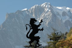 Lion and mountain. Iron lion with mont blanc in the background Stock Photos