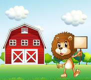 A lion near the barn holding an empty signboard Royalty Free Stock Photos